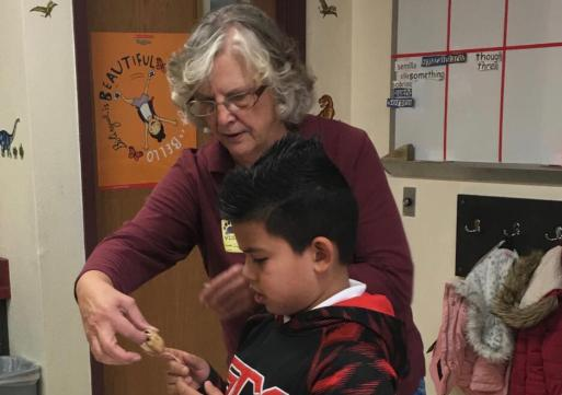 Long-time volunteer Donna assists a student in during a classroom program